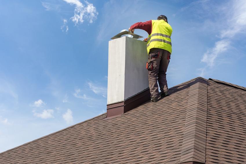 Mężczyzna wykonujący prace przy kominie na dachu, a także ocieplenie komina i izolacja komina