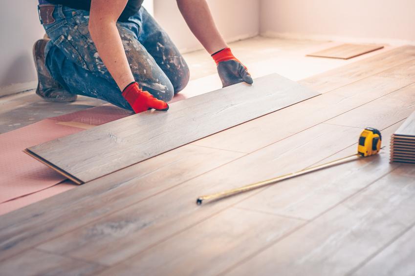 Mężczyzna układający podłogę z paneli, a także panele podłogowe i ich rodzaje