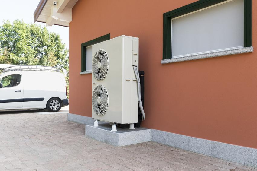 Powietrzna pompa ciepła na pomarańczowej ścianie domu oraz ogrzewanie pomą ciepła