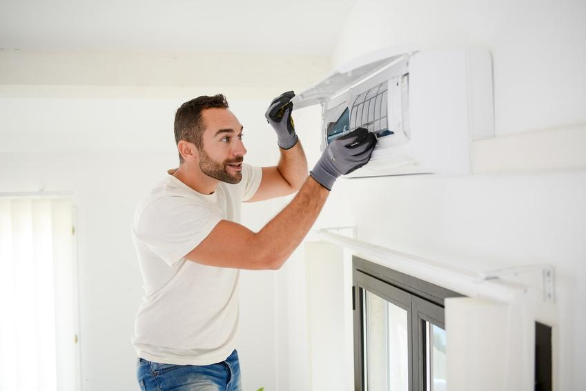 Mężczyzna podczas czyszczenia klimatyzacji, czyli odgrzybianie klimatyzacji domowej