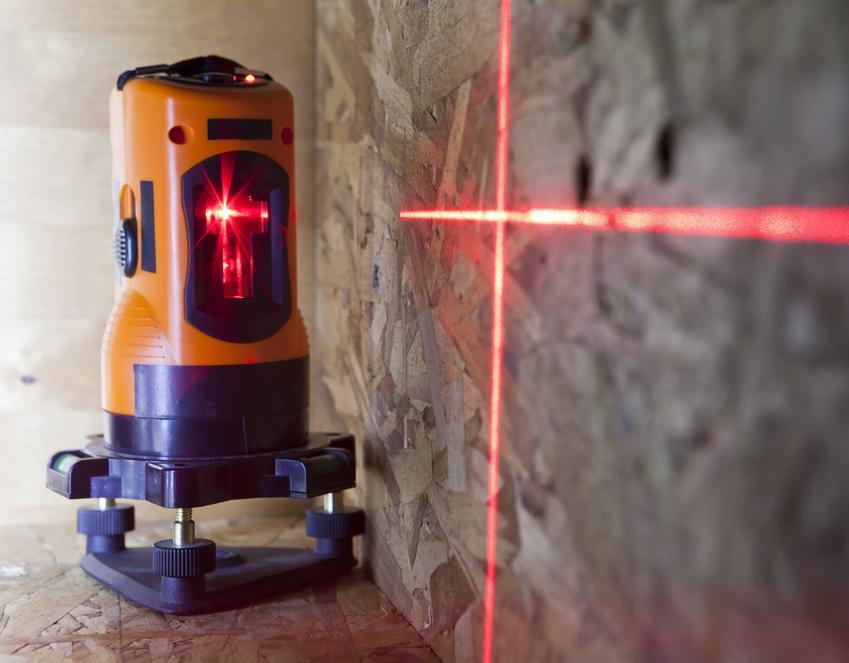 Niwelator laserowy podczas wykonywania pomiaru, a także porady zakupowe i ceny