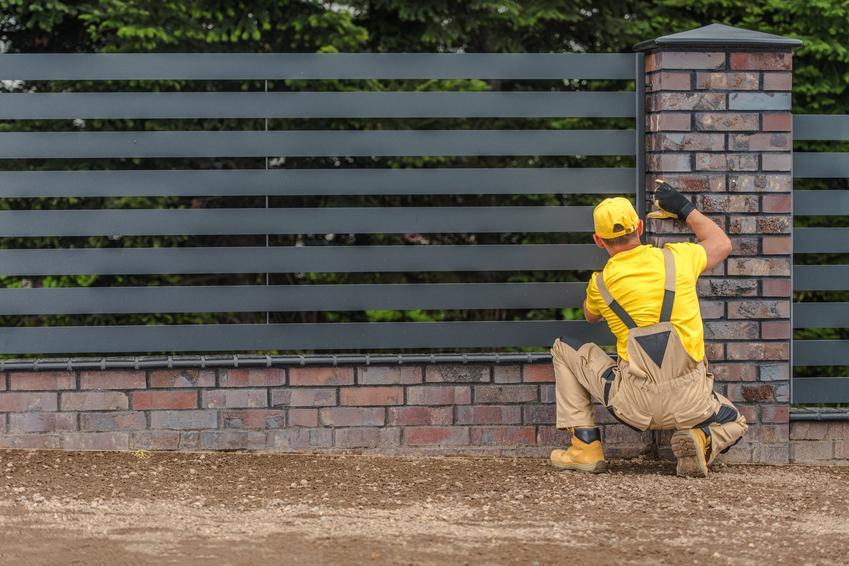 Mężczyzna przy ogrodzeniu, a także budowa ogrodzenia i zgłoszenie budowy