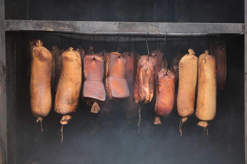 Szynki i mięsa w wędzarni ogrodowej przygotowane domowym sposobem wiszące na ruszcie nad paleniskiem w oparach dymu
