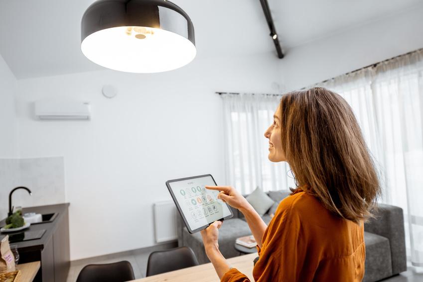 Kobieta sterująca oświetleniem w domu oraz automatyka domowa i inteligentny system domowy