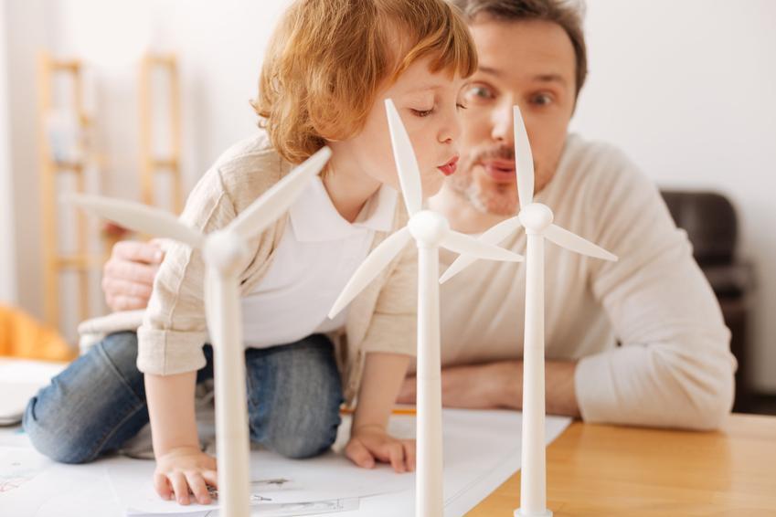 Tata z synkiem przy makiecie wiatraków, a także małe wiatraki prądotwórcze