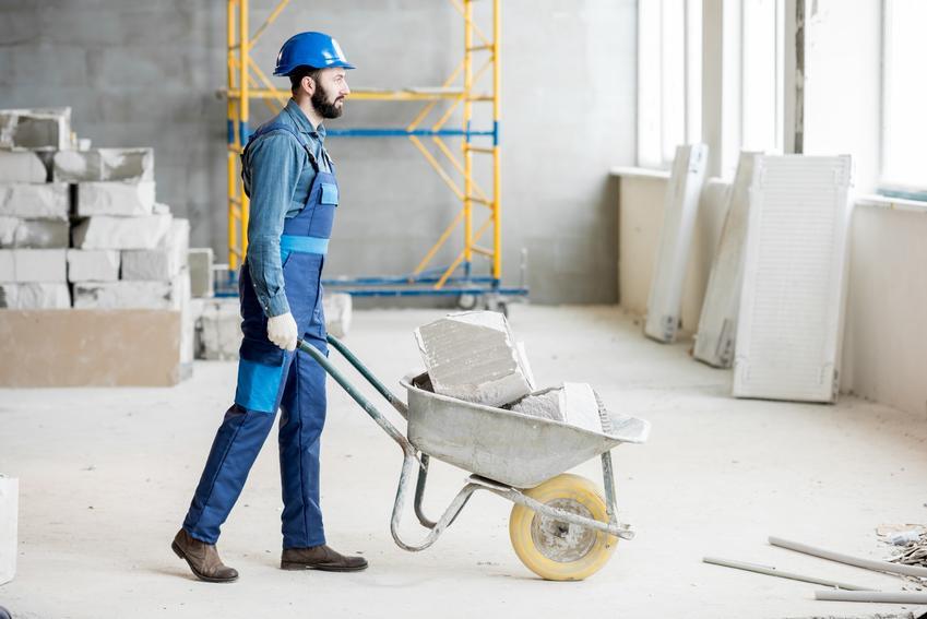 Mężczyzna z taczką na budowie, a także taczka budowlana i jej cena