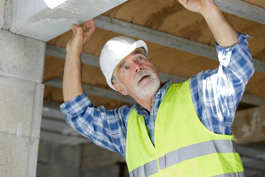 Mężczyzna montujący nadproża betonowe budowlane na placu budowy