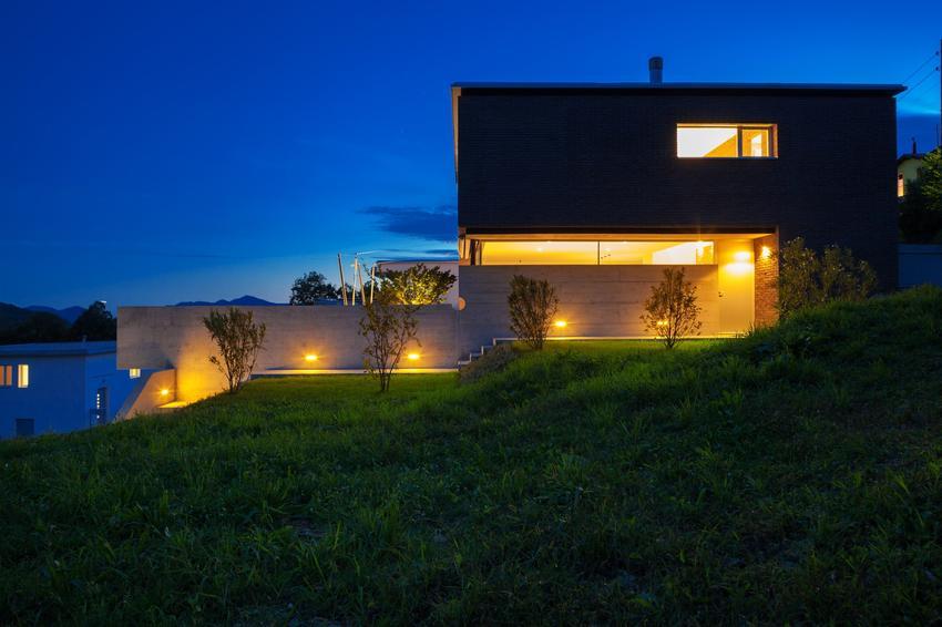 Oświetlony dom jednorodzinny, a także lampy zewnętrzne na dom, oświetlenie zewnętrzne