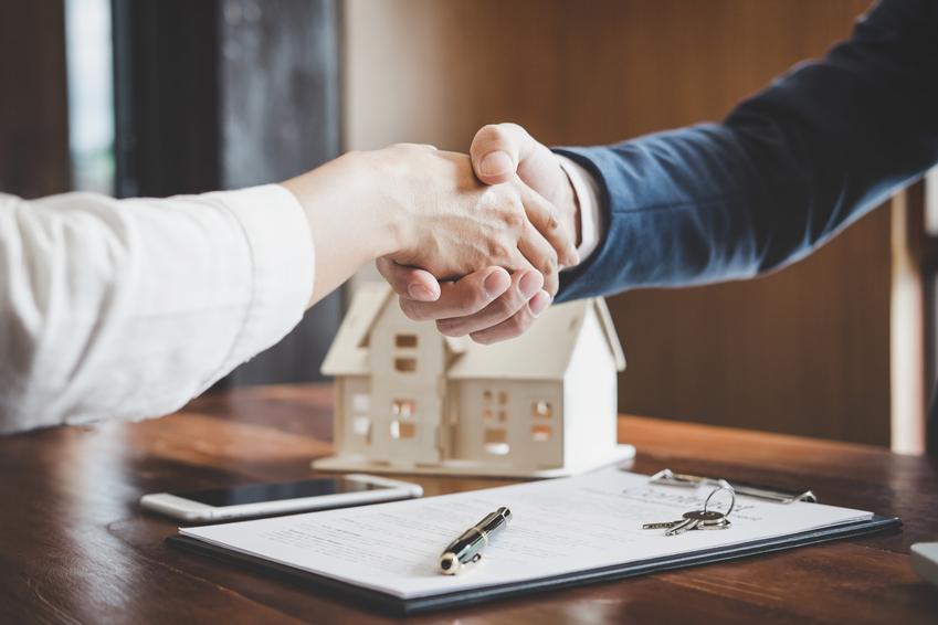 Uścisk dłoni nad umową kredytową, a także kredyt hipoteczny i jego kalkulator w 2020