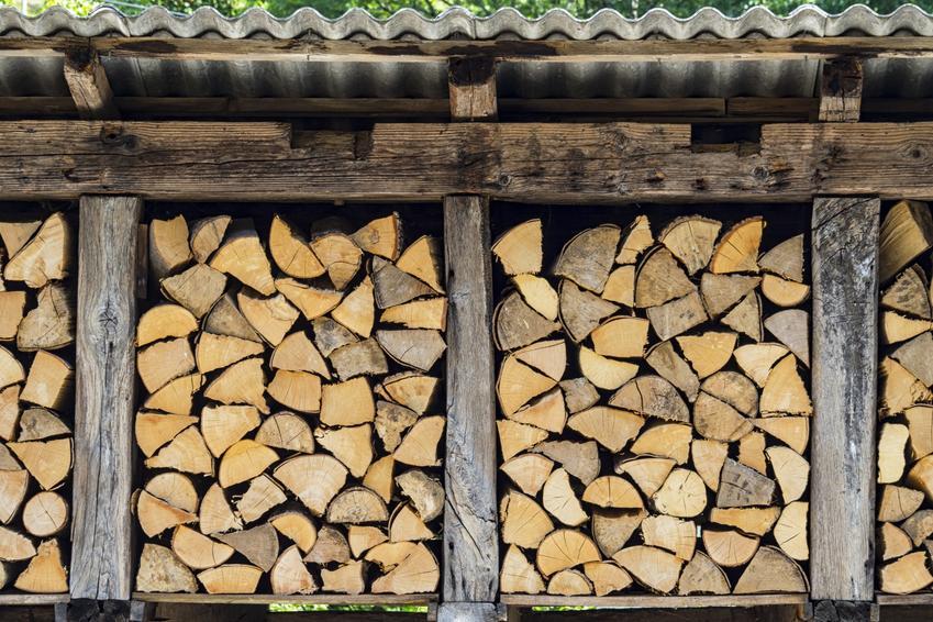 Drewutnia z palet wypełniona drewnem i porady, jak zrobić drewutnię w ogrodzie