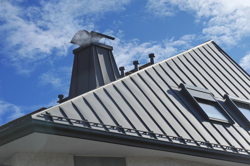 Dach z kominem na tle nieba, a także ława kominiarska, ławeczka na dachu