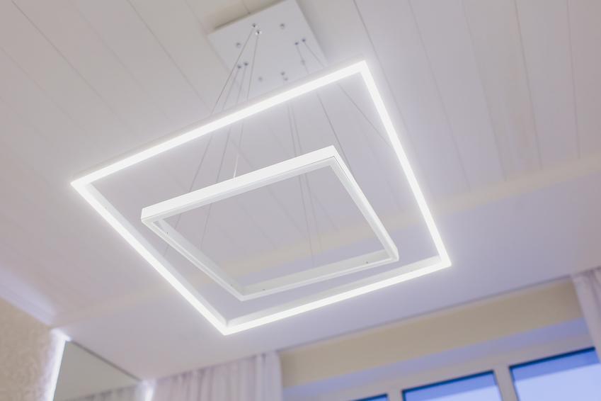 Świecący żyrandol LED na suficie w salonie, a także polecane żyrandole led