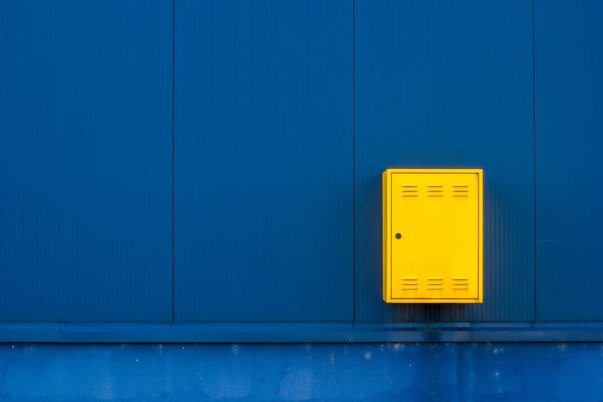 Żółta skrzynka gazowa na niebieskiej ścianie, a także szafki gazowe i ich rodzaje