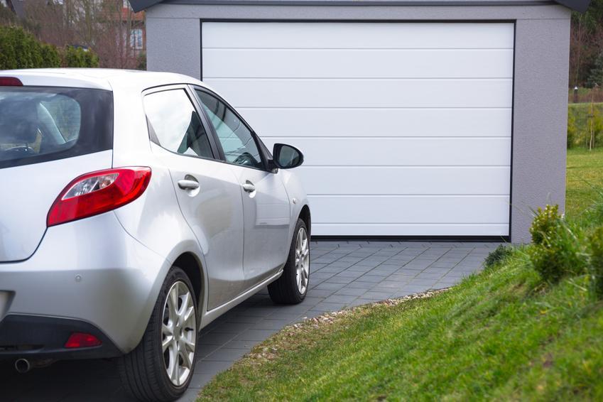 Samochód przed garażem, a także garaż z płyty warstwowej czy z płyty obornickiej