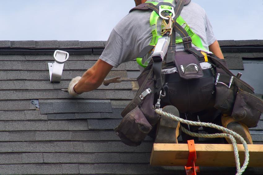 Mężczyzna pracujący na dachu, a także porady, jak naprawić przeciekający dach, cieknący dach