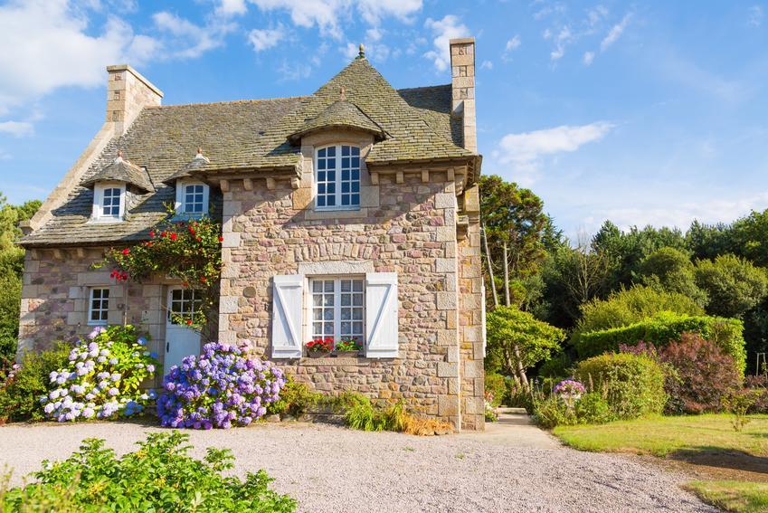 Piękny dom z kamienia na tle nieba, a także cena i projekty domów z kamienia