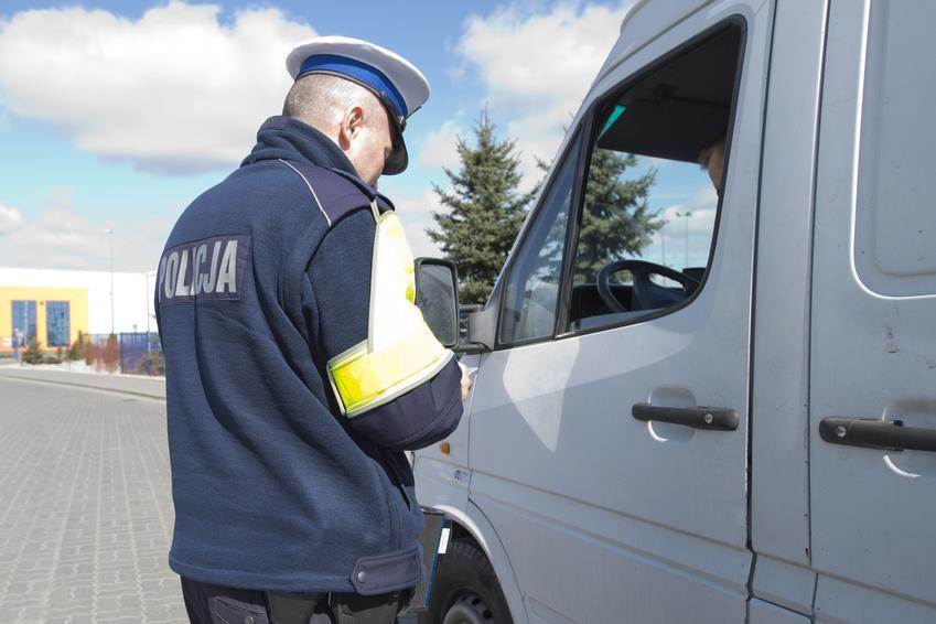 Policjant przy samochodzie oraz jaki mandat za przekroczenie prędkości i liczba punktów karnych