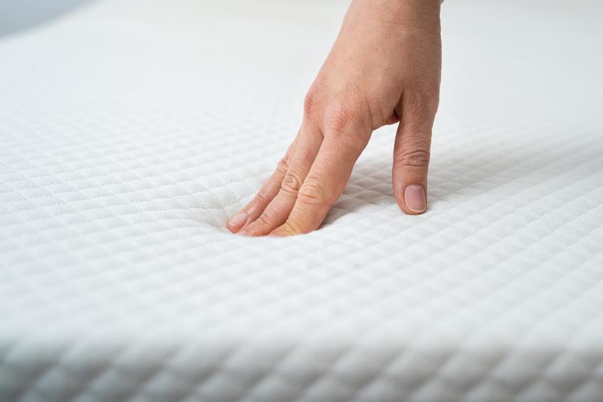Dłoń dotykająca materaca, a także materace latekstowe, materace sprężynowe i inne materace Jysk