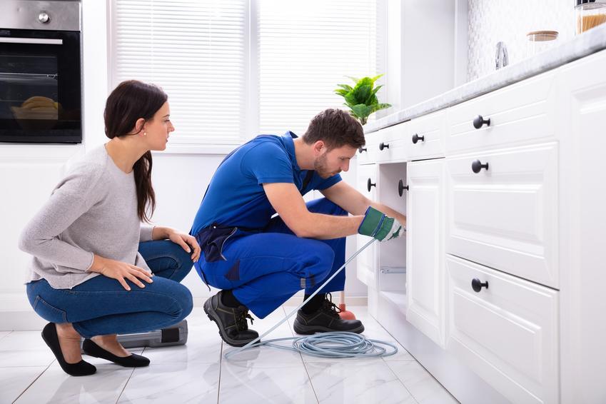 Mężczyzna podczas naprawy zlewu, a także jak udrożnić rury, czym udrożnić rury domowym sposobem