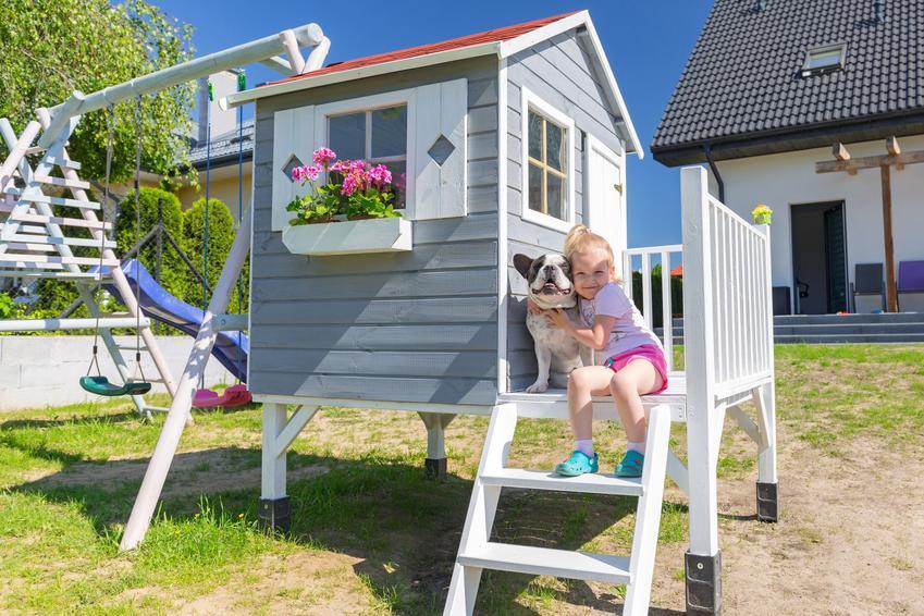 Dziecko w domku ogrodowym, a także domki ogrodowe dla dzieci, domki platikowe i drewniane