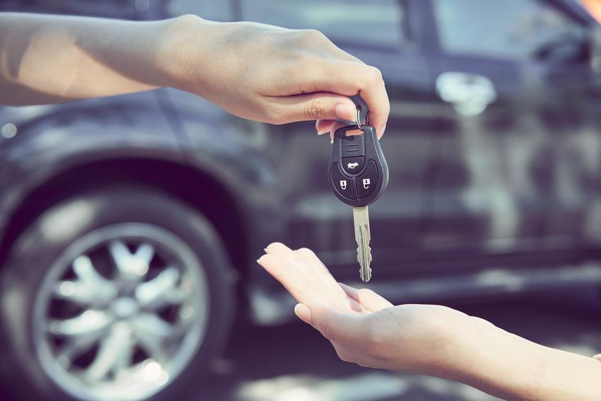 Dłonie przekazujące kluczyki do auta, a także umowa kupna sprzedaży samochodu a dwóch właścicieli