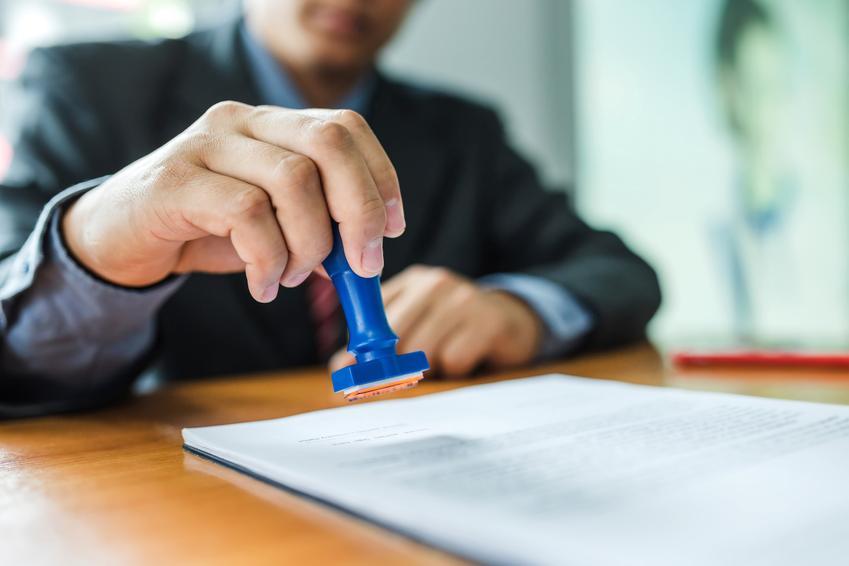 Przybijanie pieczątki na dokumencie oraz porady, jak zmienić nazwisko i zmiana nazwiska, zmiana nazwiska po rozwodzie, zmiana nazwiska dziecka