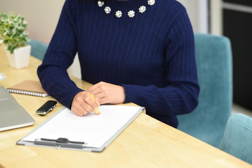 Kobieta podpisująca raport w biurze, a także protokół powypadkowy, raport powypadkowy