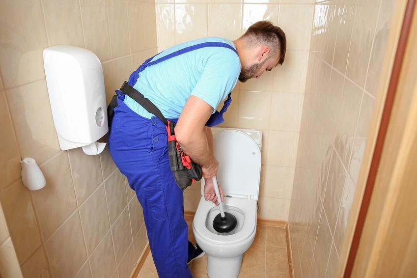 Mężczyzna podczas odtykania toalety, a także jak odetkać kibel, jak przetkać kibel, domowe sposoby