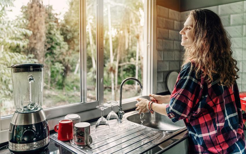 Kobieta zmywająca przy zlewozmywaku pod oknem, a także bateria kuchenna podokienna i rodzaje