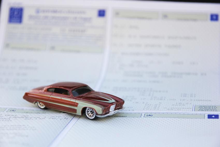 Samochód miniaturka na dokumentach oraz ile kosztuje przerejestrowanie samochodu, koszt rejestracji samochodu