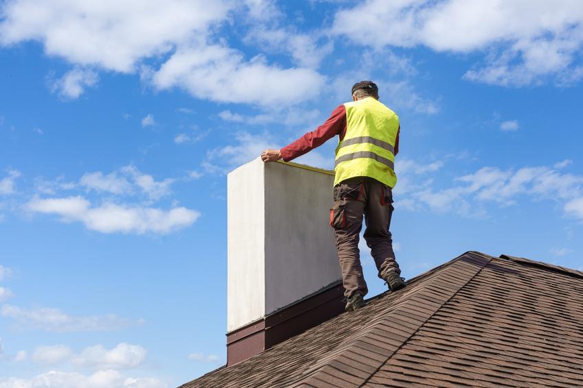 Mężczyzna pracujący przy kominie oraz szlamowanie komina, uszczelnenie komina, uszczelnianie przewodów kominowych