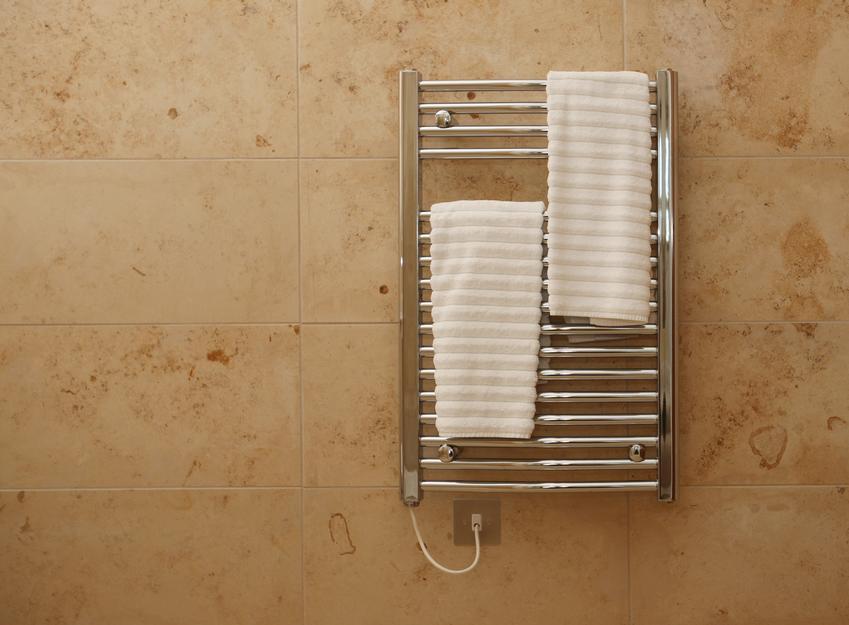 Kaloryfer na ścianie w łazience, a także grzałka elektryczna do wody i do kaloryfera