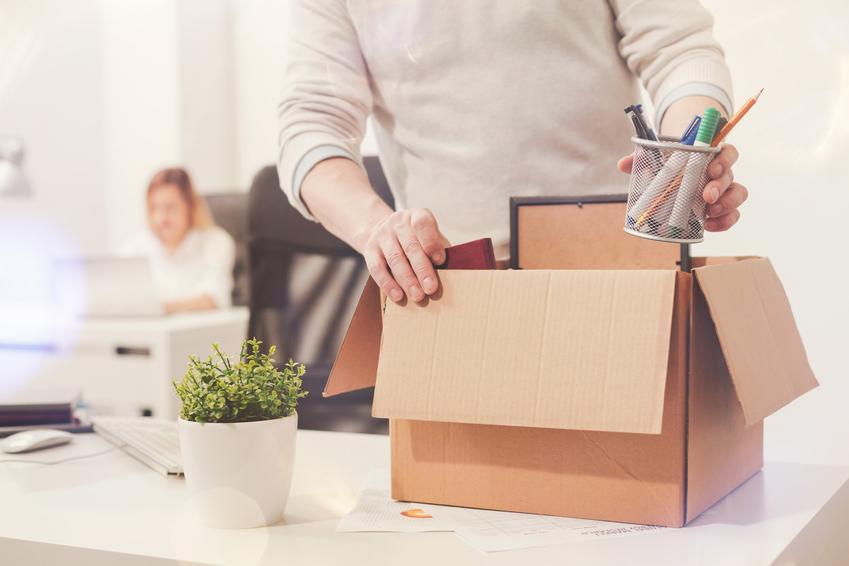 Pracownik pakujący swoje rzeczy oraz wypowiedzenie umowy o pracę przez pracodawcę