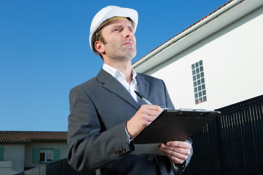 Mężczyzna w kasku przed domem oraz rozgraniczenie nieruchomości, rozgraniczenie działek