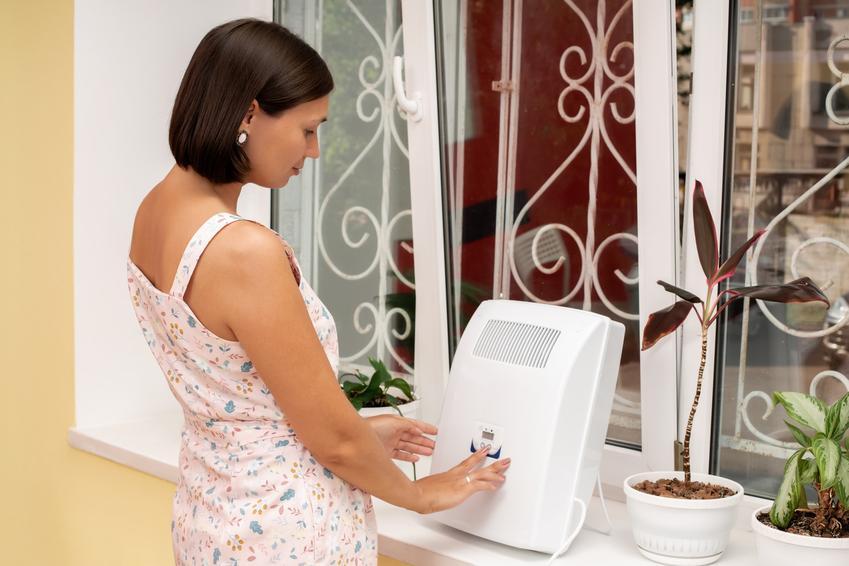 Kobieta przy klimatyzatorze w domu oraz klimatyzator stojący, klimatyzator przenośny, opinie i cena