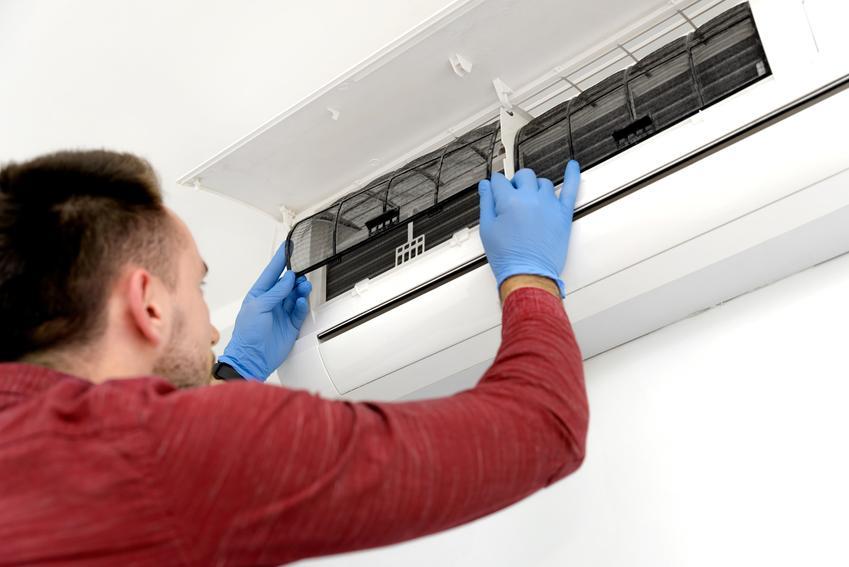 Mężczyzna podczas montażu klimatyzacji, a także jak działa klimatyzacja, zasada działania, schemat działania klimatyzacji