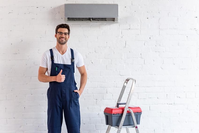 Robotnik podczas montażu klimy w domu, a także jak działa klimatyzacja, zasada działania, schemat działania klimatyzacji