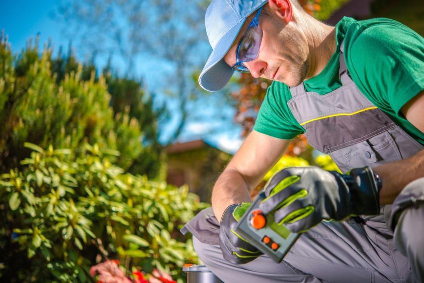 Mężczyzna montujący system nawadniania w ogrodzie, a także jakie sterownik nawadniania wybrać