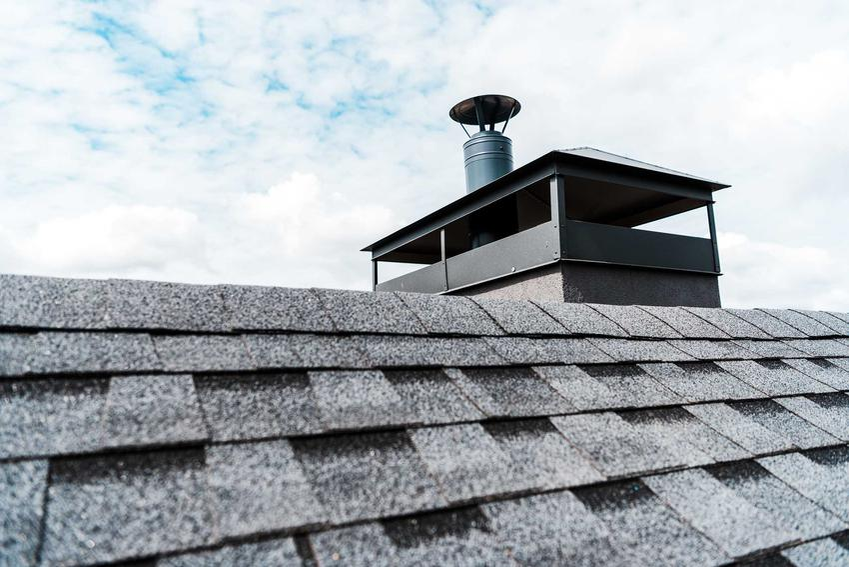 Daszek na komin w formie prostej osłonki na dachu pokrytym gontem, a także inne rodzaje i ceny daszków na komin