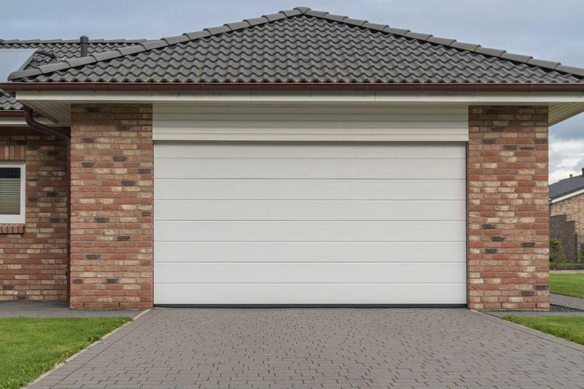 Biała brama segmentowa w muroawnym garażu, a także rodzaje, ceny, akcesoria i zastosowanie