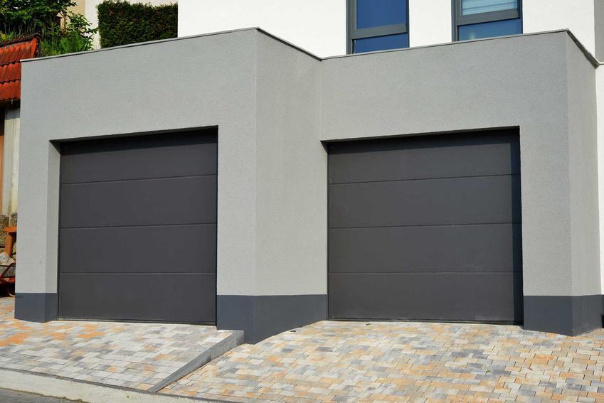 Czarne bramy segmentowe garażowe w szarych garażach, a także ceny, rodzaje, akcesoria i zastosowanie