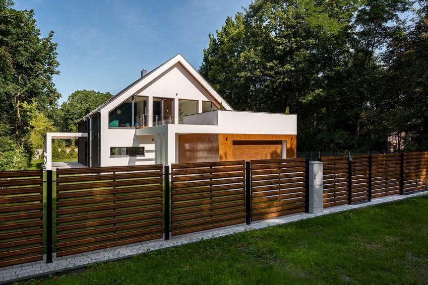 Nowoczesne ogrodzenie panelowe z drewna przed nowoczesnym dodmem biało-brązowym, a także inne nowoczesne ogrodzenia, rodzaje i ceny