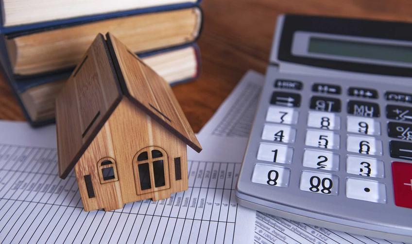 Kalkulator obok makiety domu, a także informacje o zmianie prawa budowlanego 2021 r., przez które budowa domu będzie droższa