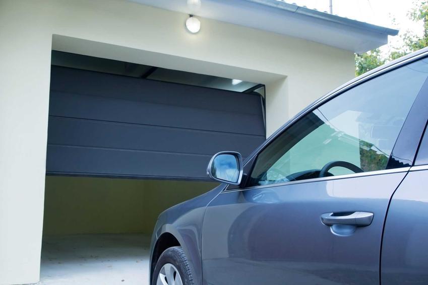 Uchylna brama garażowa i wjeżdżający do niej samochód, a także ceny, rodzaje, zastosowanie oraz montaż krok po kroku