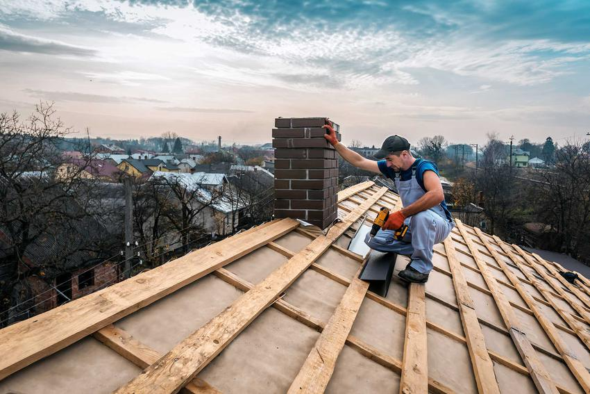 Fachowy dekarz na dachu budynku zaczynający wykonywać pokrycie dachowe, a także jak znaleźć dobrego fachowca dekarza, a także jak sprawdzić referencje