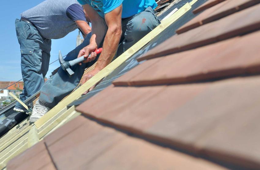 Dekarz siedzący na dachu i zajmujacy się układaniem dachówek, a także jak znaleźć dobrego fachowca, jak sprawdzić jego referencje