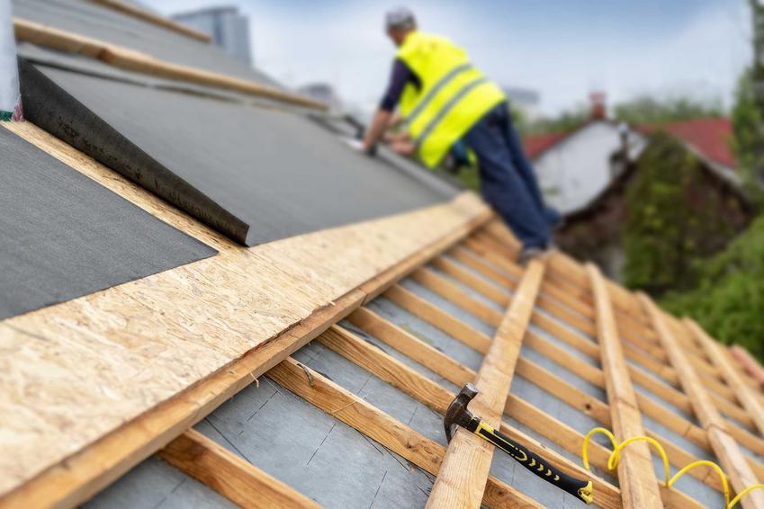 Mężczyzna kładący membranę pod dach, a także inne etapy konstrukcji dachu, ceny, materiały oraz rodzaje dachów