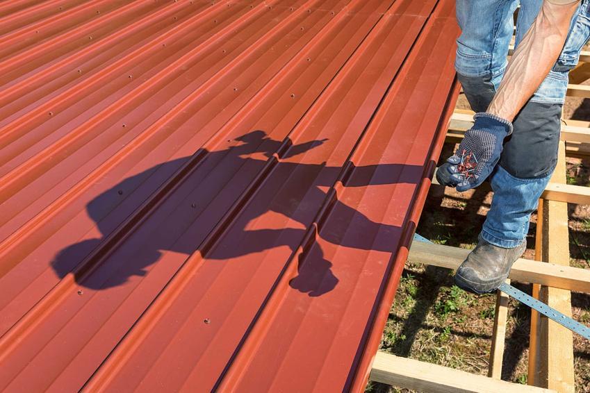 Mężczyzna wykonujący obróbki blacharskie na dachu domu jednorodzinnego krok po kroku, a także rodzaje, oraz na czym polegają obróbki blacharskie
