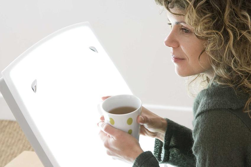Kobieta siedząca wygodnie z kubkiem herbaty w dłoniach przy lampie antydepresyjnej, a także informacje o lampach, rodzaje, działanie, ceny, opinie