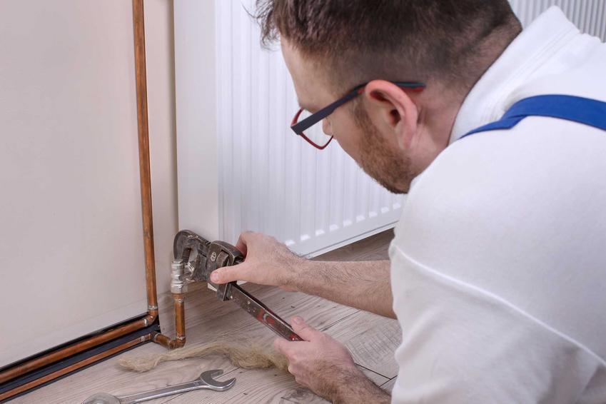 Mężczyzna zajęty odpowietrzaniem grzejników, a także jak odpowietrzyć grzejniki w domu krok po kroku